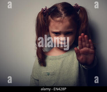 Kid girl showing hand signaling to stop violence and pain and looking down on dark background. Closeup color portrait - Stock Photo