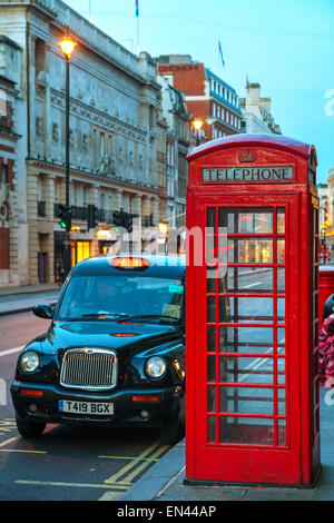 LONDON - APRIL 12: Famous red telephone booth and taxi cab on April 12, 2015 in London, UK. - Stock Photo