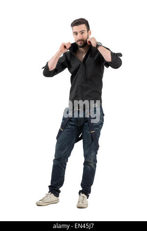 Handsome bearded young man adjusting collar on his black shirt. Full body length portrait isolated over white background. - Stock Photo