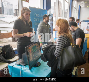 A job seeker speaks with a Via employee at the TechDay New York event on Thursday, April 23, 2015. Thousands attended - Stock Photo