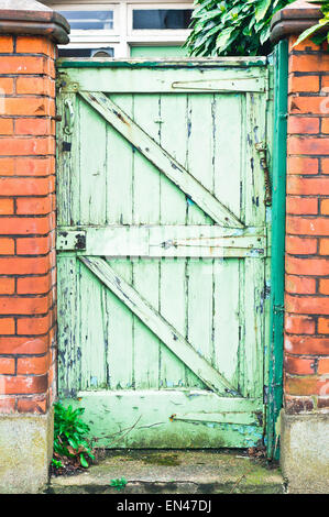 A weathered wooden garden gate in a red brick wall in the UK - Stock Photo