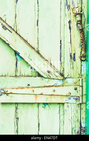 The hinge of a weathered green wooden gate - Stock Photo