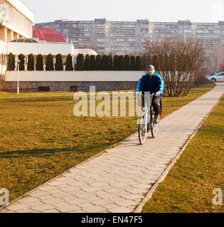 elderly man wearing glasses, a blue jacket, black trousers and a gray hat riding a bicycle on the sidewalk of concrete - Stock Photo