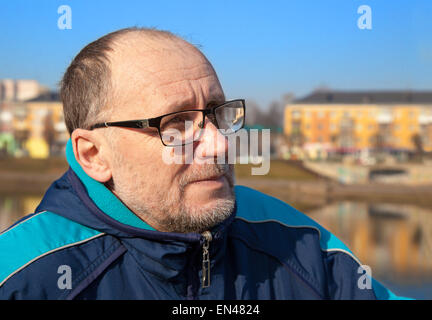 portrait of elderly man wearing glasses and a blue jacket in a city park - Stock Photo