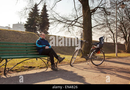 elderly man wearing glasses, black trousers and a blue jacket sitting on a bench near his bicycle in a city park - Stock Photo