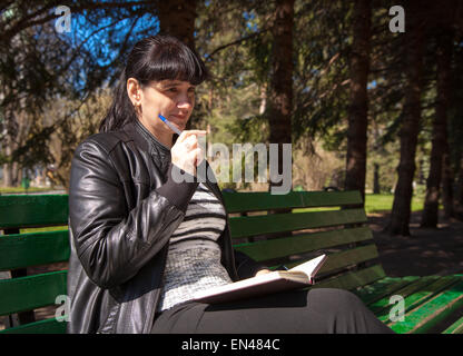 young beautiful woman in a black leather jacket and black pants sitting on a park bench holding a pen and notebook - Stock Photo