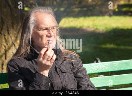 portrait of elderly gray-haired man in glasses, black jacket smoking a cigarette sitting on a bench in city park - Stock Photo