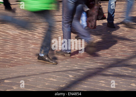 feet of pedestrians in a crosswalk in the city center on sunny spring day - Stock Photo