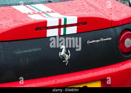 Red ferrari luxury cars badge on rear bonnet with stripes - Stock Photo