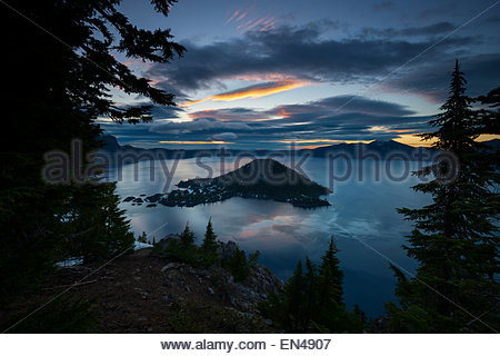 A hint of golden sunrise shines through the dark storm clouds hovering over Crater Lake in Crater Lake National - Stock Photo