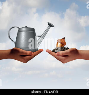 Watering can investing business concept as a two diverse human hands holding a water pot and an acorn seed in fertile - Stock Photo