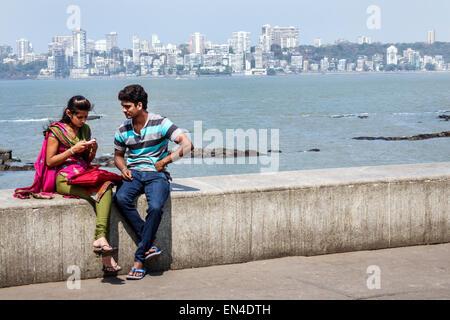 Mumbai India Asian Churchgate Marine Drive Back Bay Arabian Sea man woman couple romantic Malabar Hill skyline buildings - Stock Photo