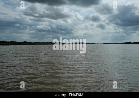 Dramatic threatening clouds forming over open brown water during a storm build-up, St Lucia estuary, KwaZulu-Natal, - Stock Photo