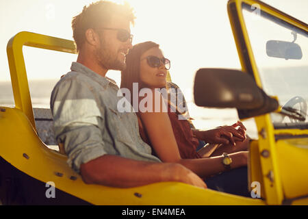 Portrait of beautiful young couple sitting together in a car. Romantic young couple enjoying the each others company - Stock Photo