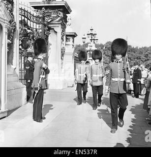 The Coldstream guards seen here mounting the guard at Buckingham Palace. The guardsmen on the right are marching - Stock Photo