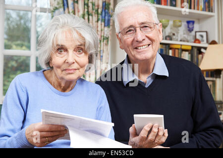 Portrait Of Smiling Senior Couple Reviewing Home Finances - Stock Photo