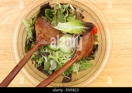 Closeup of a salad in a bowl with wooden salad servers - Stock Photo