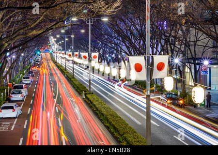 Harajuku, Tokyo, Japan traffic flows below Japanese flags at night. - Stock Photo