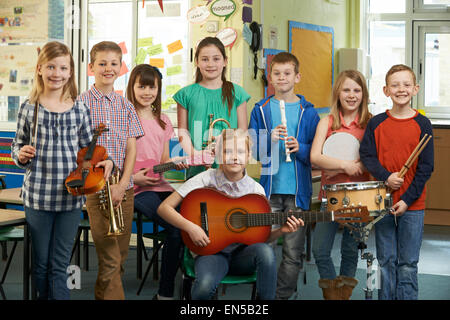 Portrait Of Students Playing In School Orchestra Together - Stock Photo