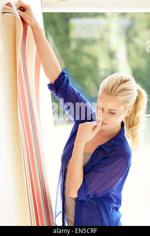 Woman holding up wallpaper sample - Stock Photo