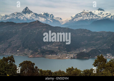 Phewa lake in Pokhara, Nepal with the city and Annapurna range of the Himalayas in the background - Stock Photo