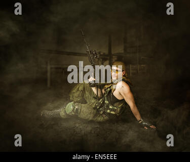 Military man soldier Holding automatic machine gun and sitting on a ground - Stock Photo
