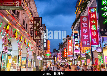 Pedestrians pass through Shangxiajiu Pedestrian Street in Guangzhou, China. - Stock Photo