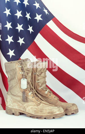 Old combat boots and dog tags with American flag in the background - Stock Photo