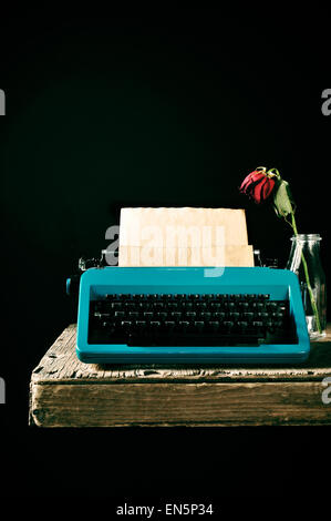 an old blue typewriter with a blank page in its roller and a wilted red rose in a glass vase on a rustic wooden - Stock Photo