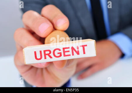 a young caucasian man at his office desk with a rubber stamp with the word urgent - Stock Photo