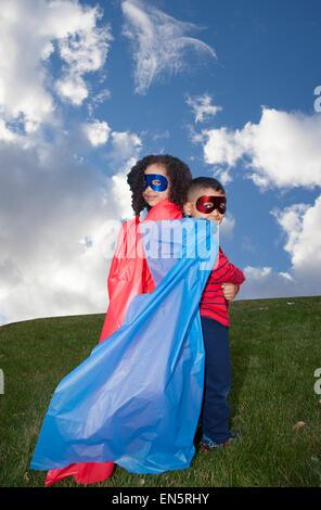 little boy and girl superheros against blue sky - Stock Photo