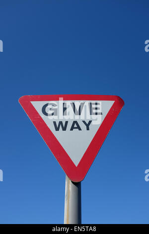 Give Way road sign against a blue background UK - Stock Photo