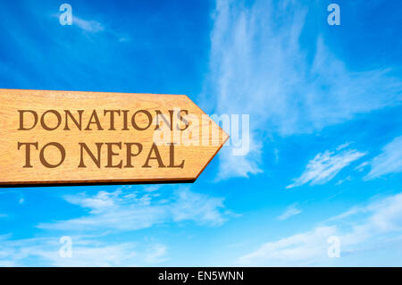 Wooden arrow sign with message DONATIONS TO NEPAL against clear blue sky with copy space available. Travel destination - Stock Photo
