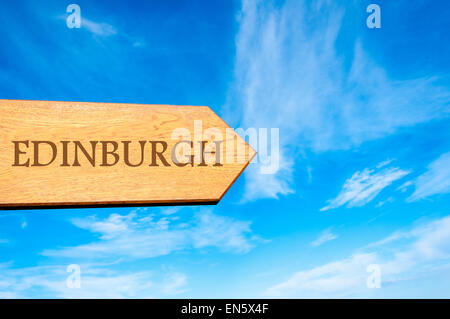 Wooden arrow sign pointing destination EDINBURGH, SCOTLAND against clear blue sky with copy space available. Travel - Stock Photo