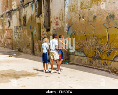 Three Cuban boys throw a ball against a wall in an alleyway in Havana Viieja. - Stock Photo