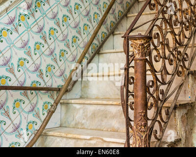 A detail of the interior of an old Havana home with classic tile work on the wall, marble steps and a wrought iron - Stock Photo