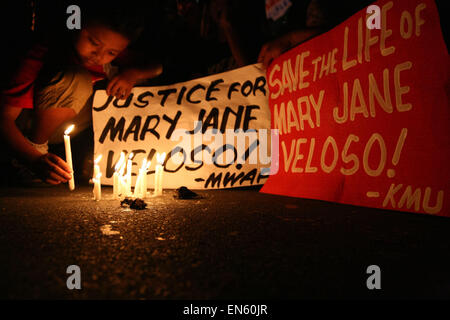 Makati, Philippines. 28th Apr, 2015. A young kid light up candles in front of the Indonesian embassy. Protesters - Stock Photo