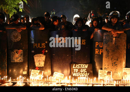 Makati, Philippines. 28th Apr, 2015. Protesters light up candles in front of the police line outside the Indonesian - Stock Photo
