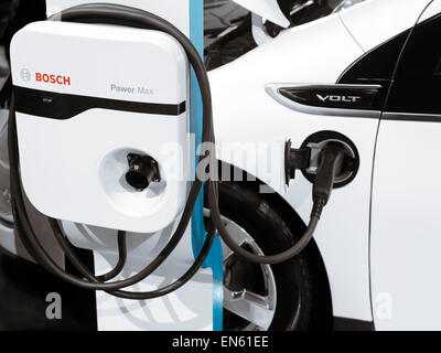 Chevrolet Volt hybrid electric car plugged in into a charging station - Stock Photo