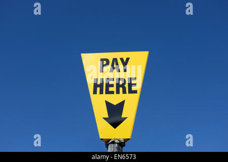 Yellow pay here sign against a blue sky background with copy space - Stock Photo