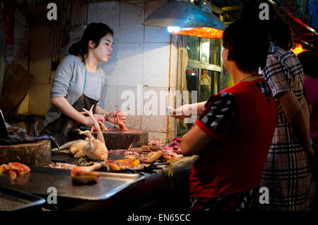 Customer buying fresh poultry from a young female butcher in an Asian market. Indoor market; Guangzhou, China; woman; - Stock Photo
