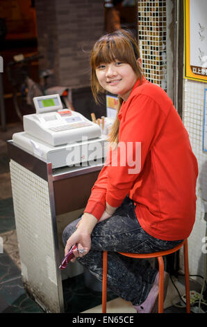 Young cheerful Chinese woman working as a cashier at a cash register in a family restaurant. China; Young lady; - Stock Photo