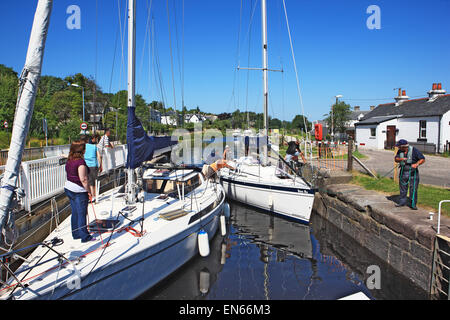 Yacht being guided by the lock keeper into lock 4 at the Ardrishaig swing bridge on the Crinan Canal in Argyllshire - Stock Photo