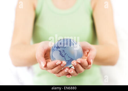 Earth Globe Protected by human hands. Glass globe in female hand.Sustainable development for the future of the our - Stock Photo