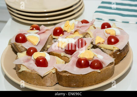Sandwiches with egg, cheese, ham and cherry tomatoes. Food and drink theme. - Stock Photo