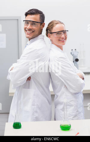 Smiling scientists standing back to back - Stock Photo