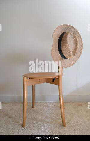 Men's straw fedora hat on chair - Stock Photo