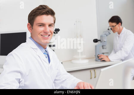 Scientist working with laptop and another with microscope - Stock Photo