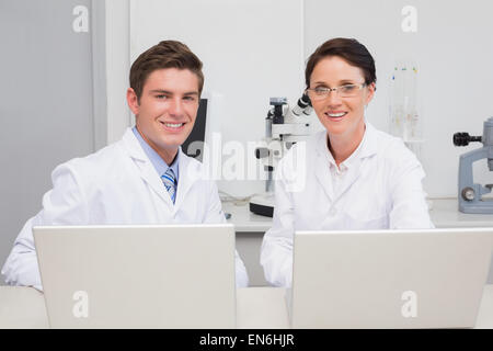 Scientists working with laptop and smiling at camera - Stock Photo