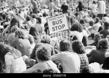 Reading Pop Festival. Festival goers with a Bus Stop sign watching the bands performing on the main stage. 24th - Stock Photo
